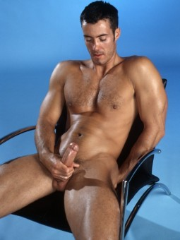 trim naked man sitting in a chair holding his big erect cock