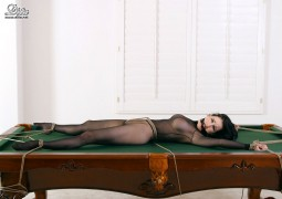 fetish image of Dita Von Teese bound to top of pool table and gaged