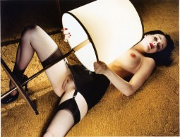 Dita Von Teese in vintage girdle lingerie holding a lighted lamp to her bare pussy