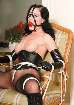 Dita Von Teese topless bound to a chair with rope and wearing a ball gag