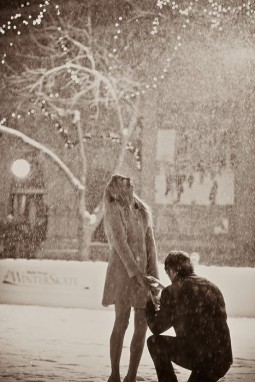 man kneeling in a snow street scene to propose to a delighted woman