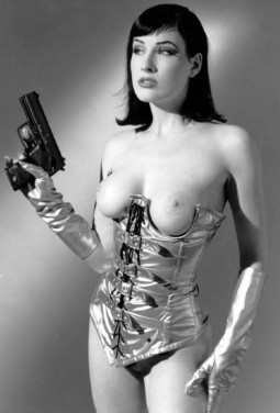 Dita Von Teese in gold corset and gloves with bare boobs brandishing a handgun