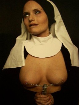 nun with her eyes rolling up and her breasts bared to show pierced nipples chained together with a crucifex pull for the chain