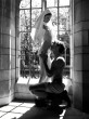 man kneeling on front of and undressing nun in a sunlight window
