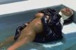 nun wearing latex habit and latex gloves laying back in a swimming pool rubbing her pussy
