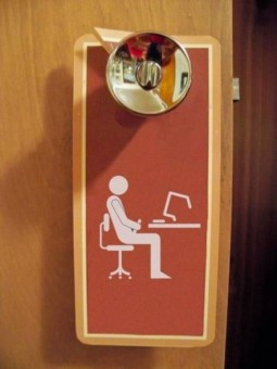 humorous image of Don't Disturb doorhanger with icon of man masturbating while sitting looking at computer