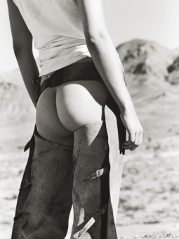 a rear view of a bareass cowgirl wearing chaps