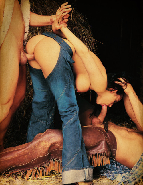 MMF threesome wtih a cowgirl in denim chaps sucking the big cock of a recling cowboy while she is fucked from behind by a second cowboy