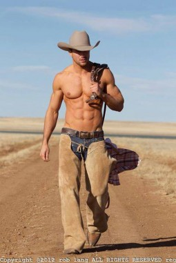 Rob Lang shirtless and wearing cowboy hat, boots and chaps walking down a dusty road