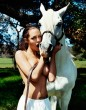 Angelina Jolie topless kissing a white stallion