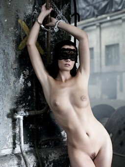 beautiful nude girl in lace mask handcuffed standing to iron beam