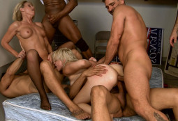 sex orgy with two women and four men on a bed fucking and sucking