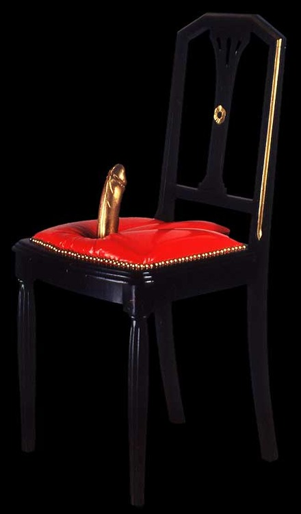 image of an elegant upholstered chair with a gold cock dildo mounted on the seat