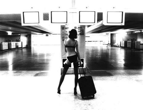 hot woman clad only in bra and panties standing alone in an airport terminal with her rollaway